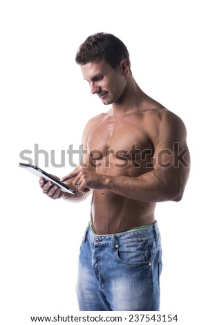 Shirtless muscular young man holding ebook reader, standing isolated on white background - stock photo