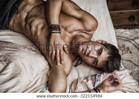 Shirtless sexy male model lying alone on his bed in his bedroom, looking at camera with a seductive attitude, shot from above - stock photo