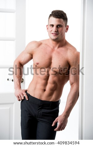 Shirtless sexy male model standing in the doorway home interior, looking to camera with a seductive attitude
