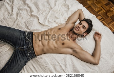 Shirtless sexy young smiling man lying alone on his bed in his bedroom, looking at camera with a seductive attitude - stock photo