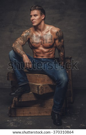 Shirtless tattooed guy in denim jeans posing on wooden boxes in studio.