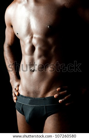 Shirtless underwear male model posing in style. Hands on waist, cropped image - stock photo