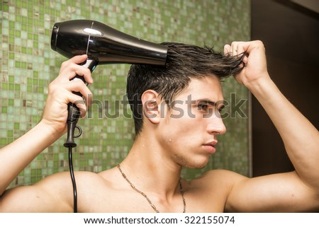 Shirtless young man drying hair with hairdryer, looking at mirror at home - stock photo