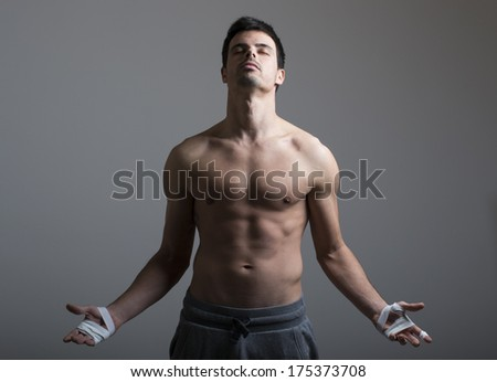 Shirtless young man meditating on a gray background