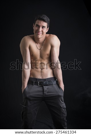 Shirtless young man outdoor doing silly face and stupid pose, on black background, studio shot