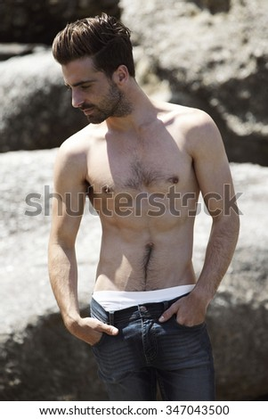 Shirtless young man posing on rocks