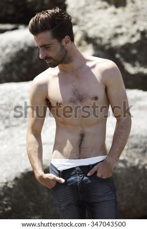 Shirtless young man posing on rocks - stock photo