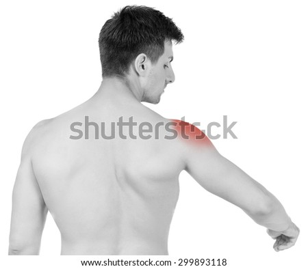 Shirtless young man suffering from shoulder pain on white background. Black and white photo. - stock photo
