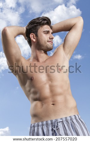 Shirtless young man with hands behind head against cloudy sky - stock photo