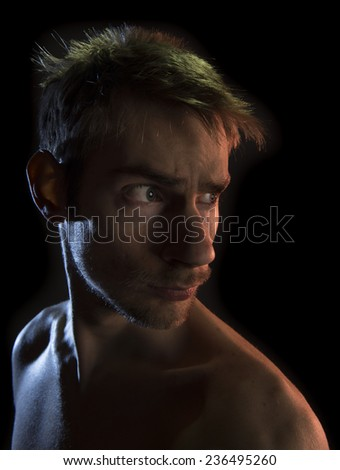 Shirtless young masculine man looking to the side over a black background. - stock photo