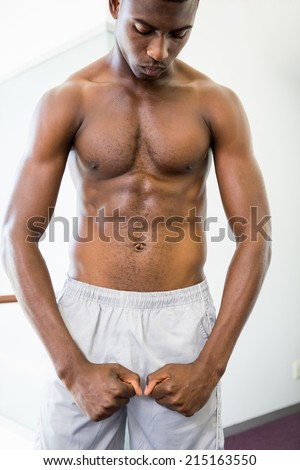 Shirtless young muscular man shouting while flexing muscles in the gym - stock photo