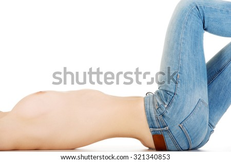 Shirtless young woman lying in jeans.