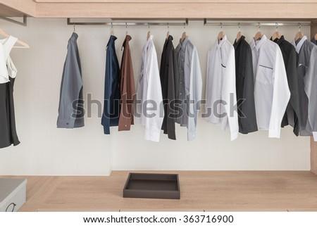 shirts hanging on rail in modern wooden wardrobe design - stock photo