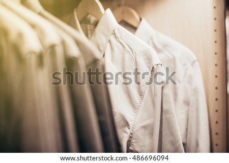 Shirts hanging stack,close up,white shirts hanging on rack
