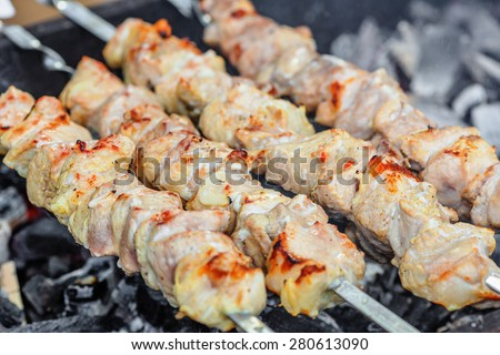 Shish kebab being roasted on skewers over charcoal - stock photo