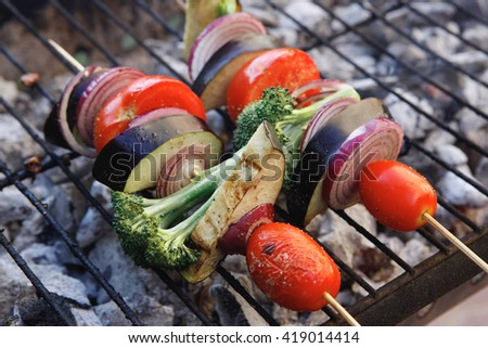 shish kebab fresh raw vegetables tomato red onion cherry broccoli eggplant on skewer over grid charcoal brazier ready to cook