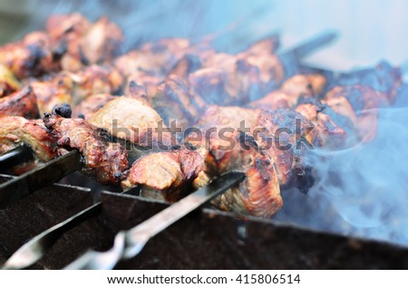 Shish kebab is prepared on skewers on the grill - stock photo