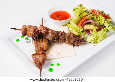 Shish kebab on a skewer lies on a pita. Near sauce and fresh vegetable salad. White background - stock photo