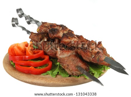 Shish kebab on a wooden support with vegetables isolated on white background - stock photo