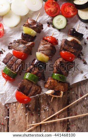 Shish kebab on skewers with vegetables close-up on the table. vertical view from above - stock photo