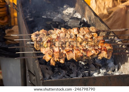 Shish kebab: slices of meat with sauce preparing on fire - stock photo