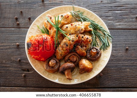 Shish kebab with baked tomato and mushrooms. Spicy shish kebab on wooden table. Homemade supper with fresh vegetables. Top view on grilled meat food - stock photo