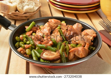 Shitake Mushroom chicken stir fry in a pan with serving plates - stock photo