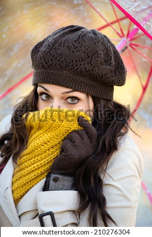 Shivering woman suffering cold autumn wind and rain. Brunette female covering her mouth with warm scarf because of fall season bad weather. - stock photo