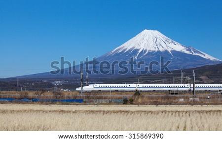Shizuoka - JAN 13: Shinkansen bullet train passed Mt. Fuji at Fuji city  in JAN 13 ,2015 , Shizuoka ,Japan. Shinkansen is world's busiest high-speed railway operated by four Japan Railways companies.  - stock photo