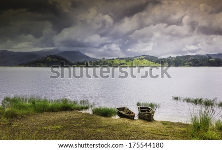 Shllong, Meghalaya, India: Two wooden boats moored on Umiam Lake as a monsoon storm threatens over the Khasi Hills near Shillong, Meghalaya, India. - stock photo