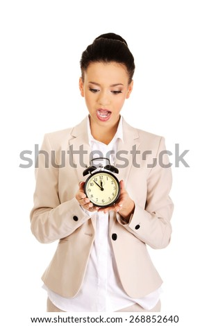 Shocked african businesswoman with alarm clock. - stock photo