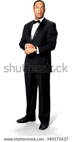 Shocked African man with short black hair in evening outfit holding wristwatch - Isolated