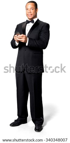 Shocked African man with short black hair in evening outfit using mobile phone - Isolated