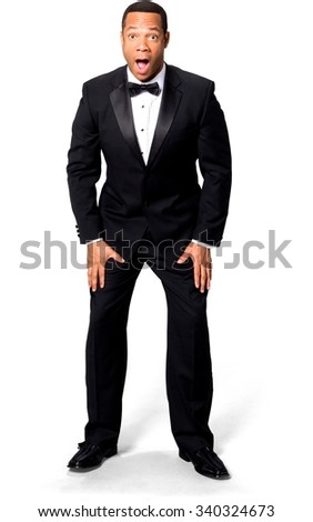 Shocked African man with short black hair in evening outfit with hands on thighs - Isolated