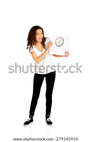 Shocked african woman holding a scale. - stock photo