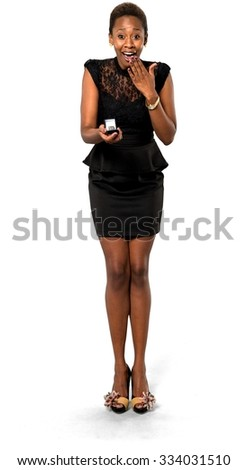 Shocked African young woman with short dark brown hair in evening outfit holding engagement ring - Isolated
