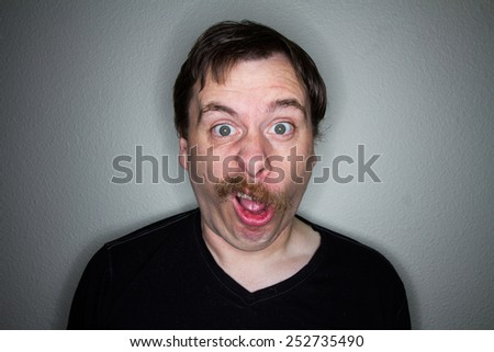 shocked, amazed face on a mustached man - stock photo