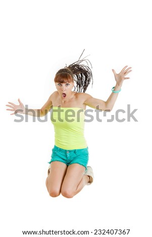 Shocked and surprised beautiful cute young woman or girl in blank green t-shirt and shorts jumps with face expression over white , teenage problems in adolescence