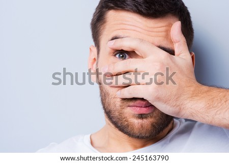 Shocked and terrified. Portrait of young man covering his face by hand and looking at camera while standing against grey background - stock photo