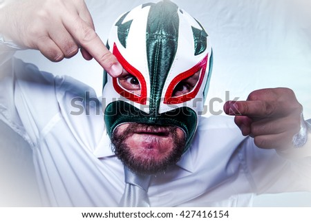 Shocked, angry businessman with Mexican wrestler mask, expressions of anger and rage - stock photo
