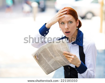 Shocked, astonished businesswoman reading newspaper, bad news outside city street background. Human face expressions, emotions, feelings, body language  - stock photo