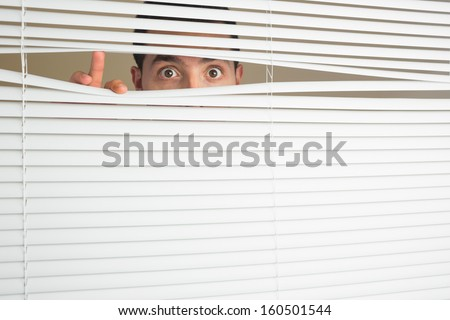 Shocked beautiful brown male eyes spying through roller blind