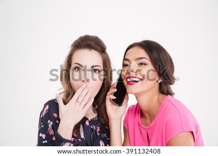 Shocked beautiful young woman overhearing conversation of cheerful female with mobile phone over white background