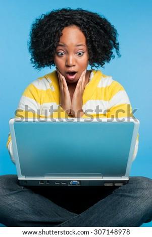 Shocked black woman using laptop computer - stock photo