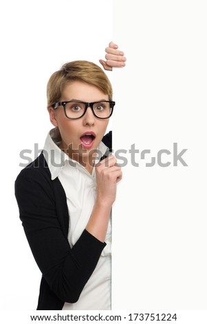 Shocked blond woman in glasses holding banner. Waist up studio shot isolated on white.