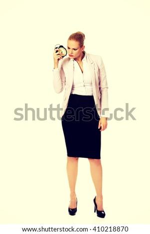Shocked business woman listening to alarm clock - stock photo
