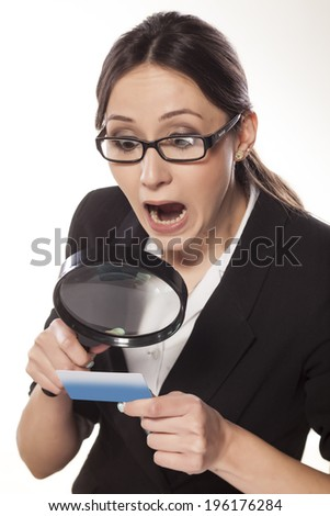 shocked business woman with a magnifying glass, looking at her credit card - stock photo