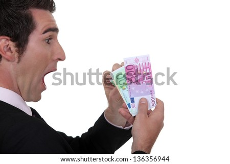 Shocked businessman counting his Euros - stock photo