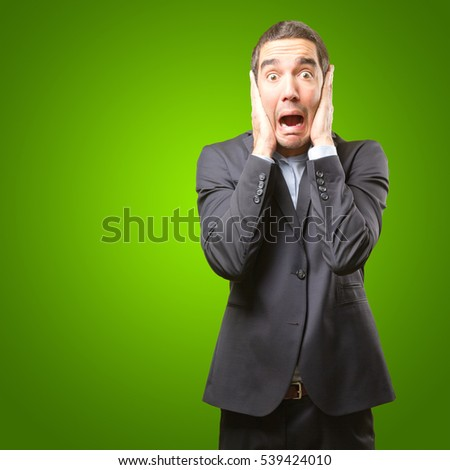 Shocked businessman covering his ears