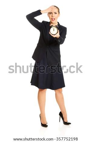 Shocked businesswoman holding alarm clock. - stock photo